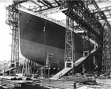 Photograph of a huge gantry with the bow of a large ship that has been painted in dark colours.