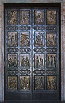 A pair of bronze doors divided into sixteen panels containing reliefs depicting scenes mainly from the life of Jesus and stories that he told.