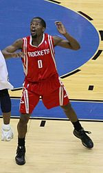 """A basketball player, wearing a red jersey with the word """"HOUSTON"""" and the number 0 on the front, stands on a basketball court."""
