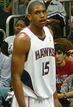"""A basketball player, wearing a white jersey with the word """"ATLANTA"""" and the number 15 on the front, stands on a basketball court."""