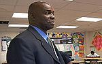 A man, wearing a black jacket with blue shirt, is standing in the middle of a classroom.
