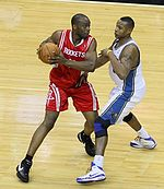 """A basketball player, wearing a red jersey with the word """"ROCKETS"""" in the front, is holding the basketball while another basketball player, wearing a white jersey, attempts to steal the ball."""