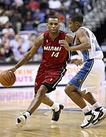 """A basketball player, wearing a red jersey with the word """"MIAMI"""" and the number 14 in the front, is dribbling the basketball while another basketball player, wearing a white jersey, attempts to defend him."""
