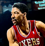 """A basketball player, wearing a red jersey with the word """"SIXERS"""" on the front, is looking to his right side."""