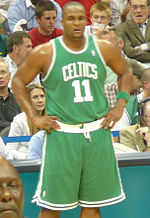 """A basketball player stands on a basketball court. He wears a green jersey with the word """"CELTICS"""" and the number 11 on the front."""