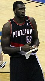 """A basketball player, wearing a black jersey with the word """"PORTLAND"""" and the number 52 on the front, stands on a basketball court."""