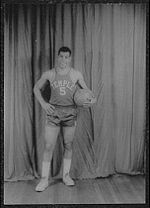 """A man, wearing a jersey with a word """"TEMPLE"""" and the number """"5"""" written in the front, is holding a basketball while posing for a photo."""