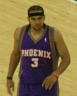 """A basketball player, wearing a purple jersey with the word """"PHOENIX"""" and the number 3 on the front, stand on a basketball court."""