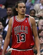 """A basketball player, wearing a red jersey with the word """"BULLS"""" and the number 13 on the front, is standing on a basketball court."""
