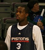 """A basketball player wearing a black jersey with the word """"PISTONS"""" and the number 3 on the front"""