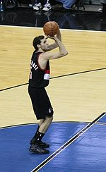 A basketball player, wearing a black jersey shooting a free throw.