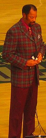 A man, wearing red and green jacket with a red shirt and tie, is standing on a basketball court while holding a microphone.