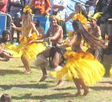 Two women in long flowing yellow skirts either side of a man in a short black skirt mid dance