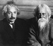 A moustached man in a lounge suit and necktie (left) sits next to a white-haired, bearded man dressed in robes (right). Both look toward the camera.