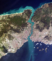 Satellite image showing an thin piece of land, densely populated on the south, bisected by a waterway