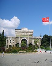 A triumphal arch adjacent to a Turkish flag and in front of an open plaza