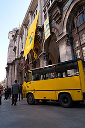 An arched neoclassical building with hanging banners, with a yellow vehicle parked in front