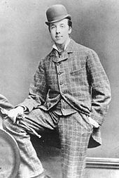 Oscar Wilde posing for a photograph, looking at the camera. He is wearing a check suit and a bowler hat. His right foot is resting on a knee high bench, and his right hand, holding gloves, is on it. The left hand is in the pocket. Oscar Wilde at Oxford.