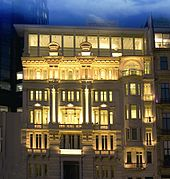 A six-story white building with light emanating from its windows under cloudy evening sky