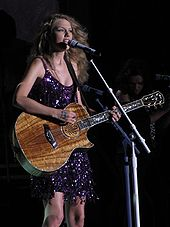 Taylor Swift performing in a dark purple dress with a light-brown colored guitar against a black background