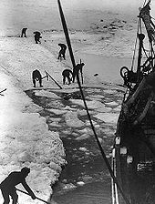 Men with digging tools removing ice surrounding the ships hull, creating an icy pool of water
