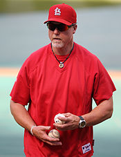 A man wearing a red shirt and St. Louis Cardinals cap holds a baseball in each hand.