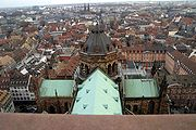 Looking down on a cruciform green-copper roof, with a tower at the centre, in the middle of a city
