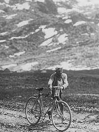 A man walking, holding, to his bicycle, on a sandy road.