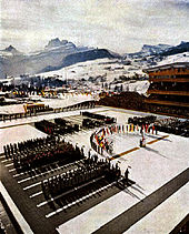 Crowds surrounding a group of flags in an open-air arena. The flags and athletes surround a rostrum. Snow-covered mountains are in the background.