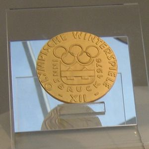 "A golden medal in display on top of a transparent support. The design on its face shows the five interlaced Olympic rings above the Games emblem which is surrounded by the words ""Innsbruck 1976"". More words are placed along the medal&squot;s rim."