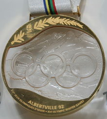 """A crystal inscribed with five rings and a mountainous background, surrounded by gold making a complete medallion. The gold is inscribed with a branch and the logo for these Games at the top, with the bottom containing the words """"ALBERTVILLE 92; XVIth Jeux Olympiques D&squot;Hiever; XVI Winter Olympic Games""""."""