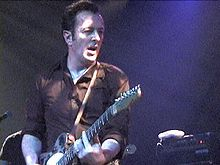 A photograph of Joe Strummer playing his guitar while performing at St. Ann's Warehouse in Brooklyn, New York City on 5 April 2002.