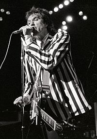 A man stands onstage with a guitar strapped across his chest. It hangs limp and unused, as he is focusing on singing into a microphone directly in front of him, which he grasps with his left hand. He wears a black-and-white, vertically striped suit.