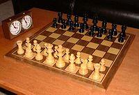 šachovnice s kameny ve výchozím postavení; vlevo šachové hodiny