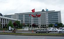 A mid-rise glass-paned office building, with an array of Turkish flags in the front.