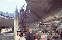 Large, underground missile silo with a missile pointing out the hole toward the sky next to a support structure. Five characters stand in the foreground.