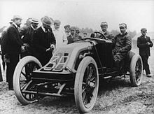 """An open-topped sports car, with """"3B"""" written on the front. A driver sits on the right side of the cockpit, and his riding mechanic sits alongside. A group of people crowd around, inspecting the car."""