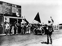 """An open-topped sports car, with """"3A"""" written on the front, crosses a white line painted on the track in front of a scoreboard, as a large black flag is waved and a crowd cheers."""