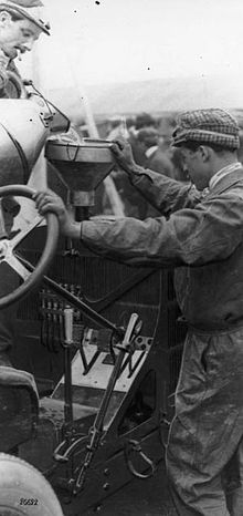 Two men pour fuel into their car using a funnel.