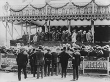 A crowd gathers in front of a canopied grandstand to watch a presentation ceremony. The bottom of the grandstand carries sponsorship by Michelin.