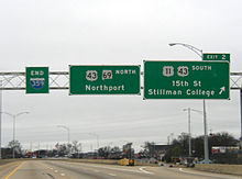 Three green signs are located above an elevated portion of roadway with no traffic visible on a cloudy day.