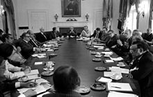 Twenty people meet in a conference room around an oval table. One man, at the center of the table on the right-hand side, is addressing the others. All are wearing suits or similar attire.