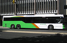 Light green, orange and white bus stopping in front of multi-story building.