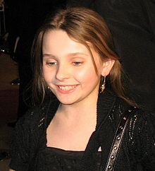 A young girl wearing a black dress looks down to her right while smiling.