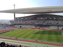 A stadium with a football pitch and track surrounded by multi-tier seating and covered by a large hanging roof