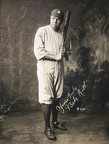 A man in full baseball attire wears a pinstriped jersey and a baseball cap. Looking to the left of the camera, he is holding a baseball bat upward.