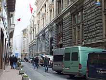 A narrow street, with parked vans and pedestrians, adorned by stone and neoclassical buildings.