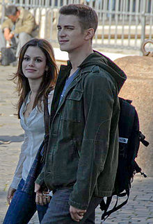 A woman and man, both smiling, are walking towards the left side of the image. The woman is wearing a white, button-up shirt and blue jeans. The man is wearing a green jacket, a blue shirt, a backpack, and blue jeans. In the background a man can be seen sitting and looking down.