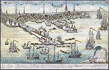 A wide view of a port town with several wharves. In the foreground there are eight large sailing ships and an assortment of smaller vessels. Soldiers are disembarking from small boats onto a long wharf. The skyline of the town, with nine tall spires and many smaller buildings, is in the distance. A key at the bottom of the drawing indicates some prominent landmarks and the names of the warships.
