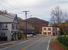 """A two-lane road curves from center bottom to center right. On the right is a gray house. Next to it is a darker gray, longer house, on a road that splits off from the one in the image. At the junction is a pale gold building with brown trim and a sign that reads """"Calsi&squot;s General Store"""". A white building and hill are in the distance behind it. Some autumn color is visible on the trees."""